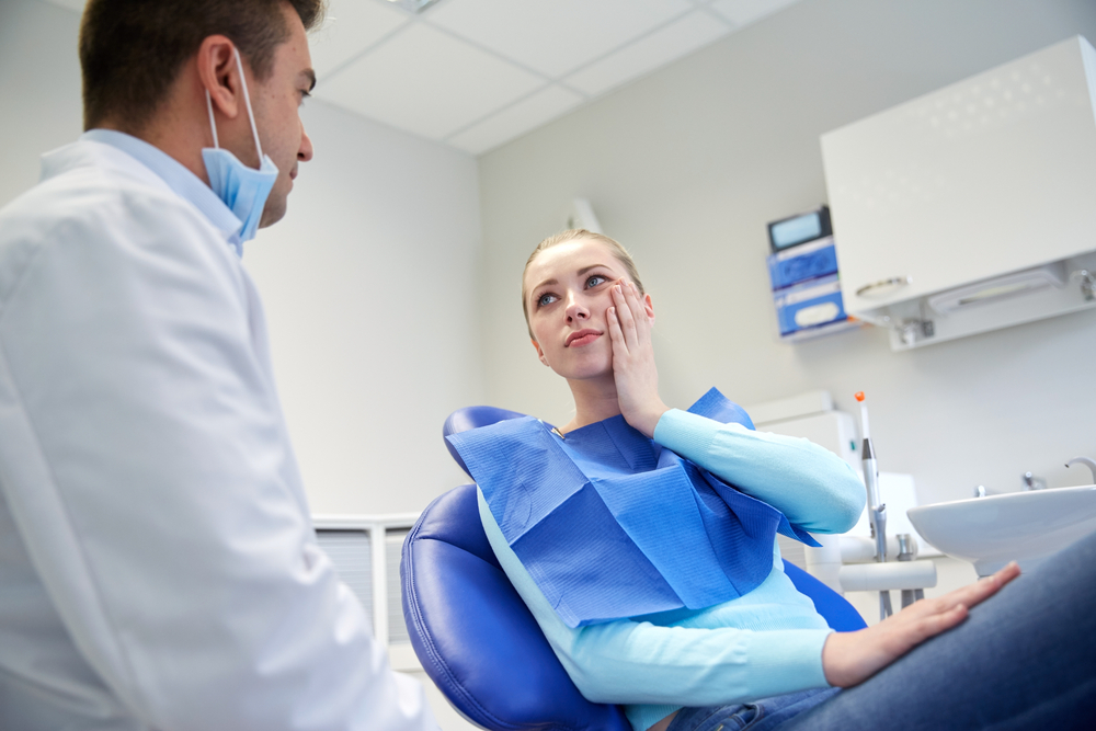 Woman patient in dental chair holding cheek toothache tooth decay talking to dentist man