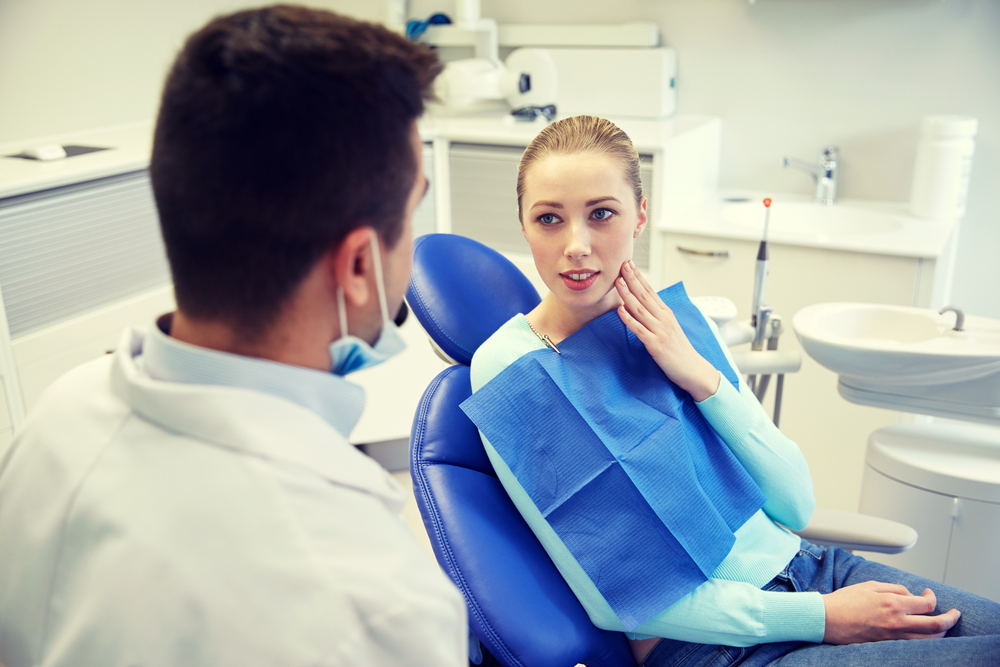Woman patient in dental chair talking with dentist while holding the side of her face