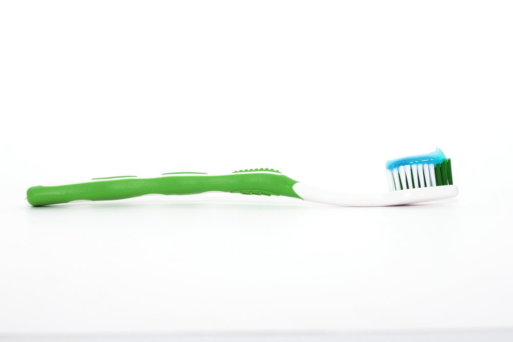Green toothbrush with blue toothpaste on bristles