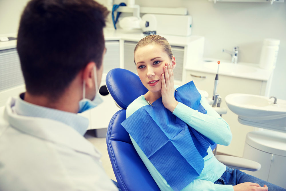 Woman patient with toothache holding cheek in dental chair talking to dentist man