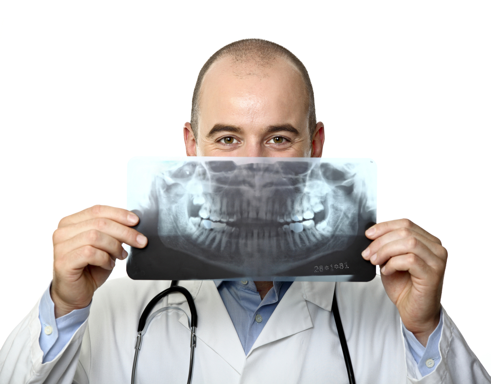 Dentist man holding up X-ray of teeth in front of his mouth