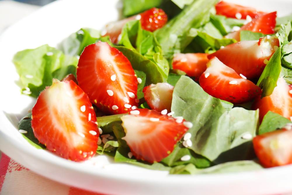 Strawberry salad with lettuce and seeds on white plate on red and white picnic tablecloth