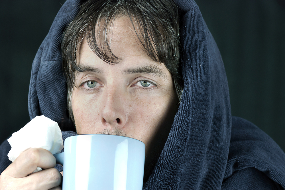 a man wearing a robe and holding a tissue is drinking ginger tea to mitigate his summertime sinuses