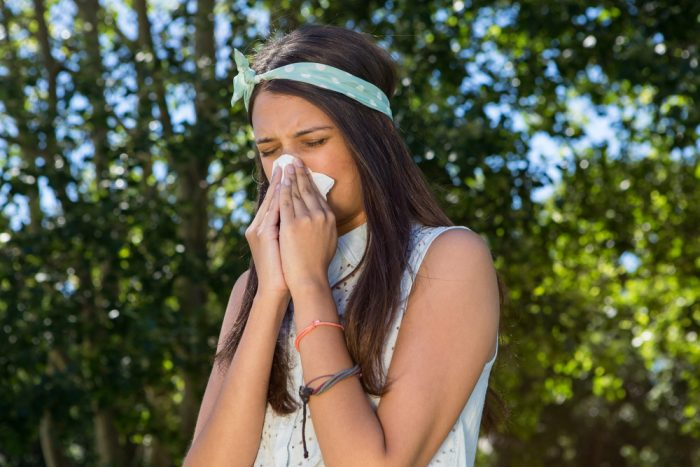 a girl surrounded by trees is sneezing due to summertime sinuses