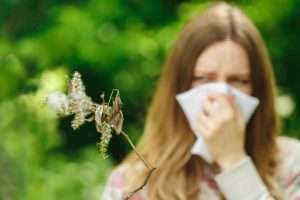 girl suffering from summertime sinuses is holding a tissue over nose staring at a pollen spreading plant