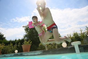 two young children jumping into a pool