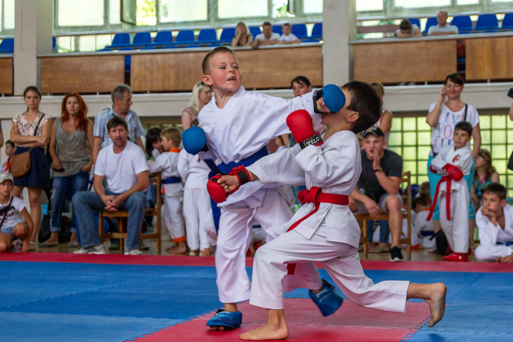 2 boys participating in karate while wearing mouthguards