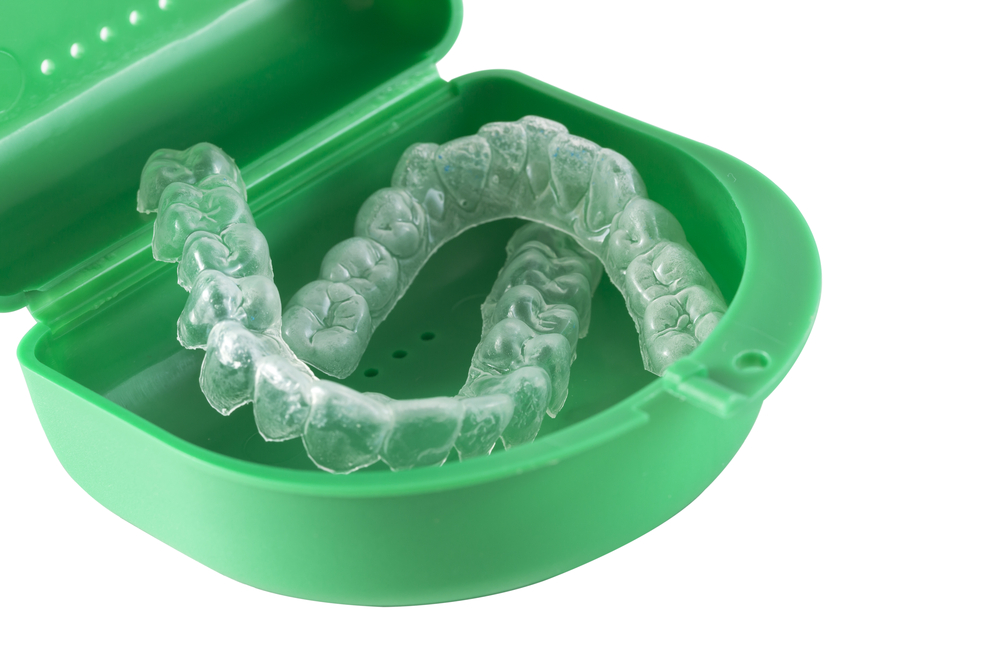 Clear dental Invisalign trays in green container case