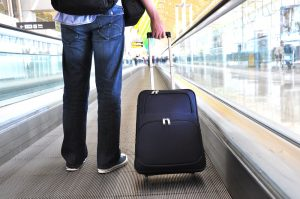 Man with backpack, carry-on bag, and suitcase on moving sidewalk in airport