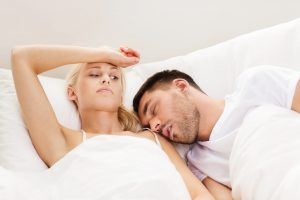 Man with OSA snoring while wife lays wide awake in bed