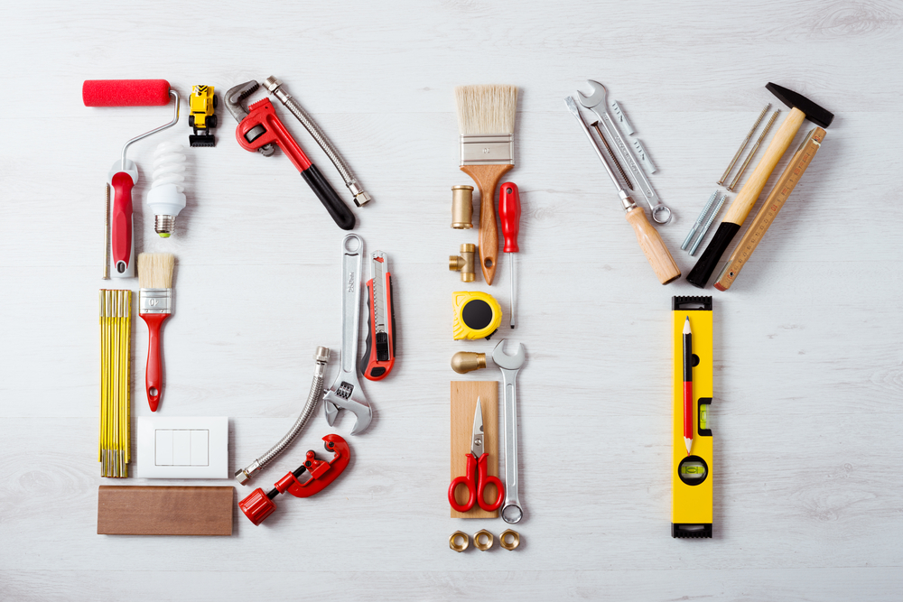DIY word composed of work and construction tools on a wooden surface top view, hobby and craft concept