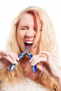 Desperate woman with toothache going to use pliers to extract her tooth