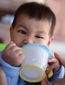 Baby drinking water from cup, South East Asian Thai baby boy