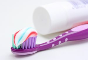 purple toothbrush and multicolored toothpaste