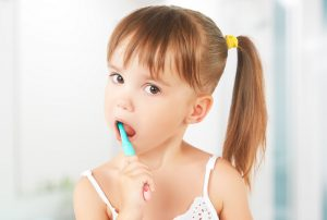 kid's dental hygiene. happy little girl brushing her teeth