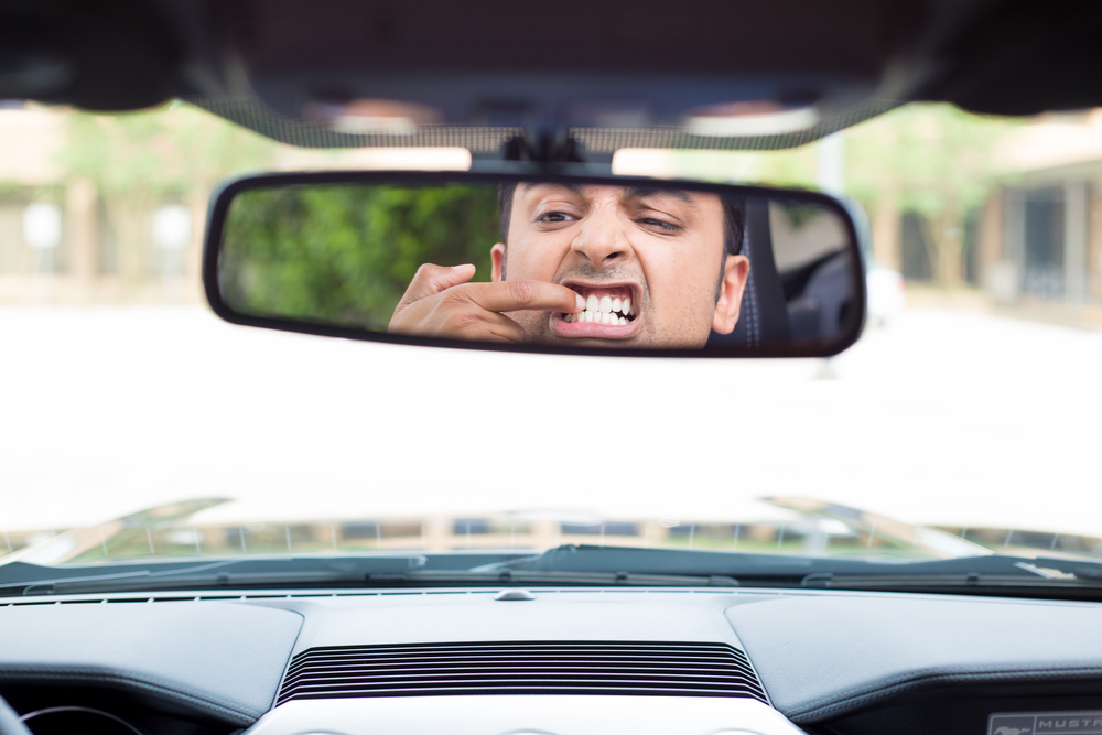 Closeup portrait, funny young man driver looking at rear view mirror to inspect his gummy smile