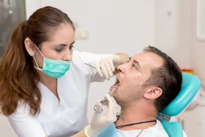 Dentist giving an injection of dental anesthesia to the patient. Young man at the dental clinic