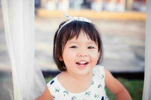 Little girl child showing front teeth with big smile: Healthy happy funny smiling face young adorable lovely female kid with new tooth dental loss: Joyful portrait of asian elementary school student